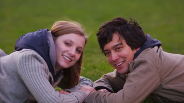Portrait of young couple laying in grass video