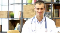 portrait of Young doctor smiling at camera in an office at the hospital video
