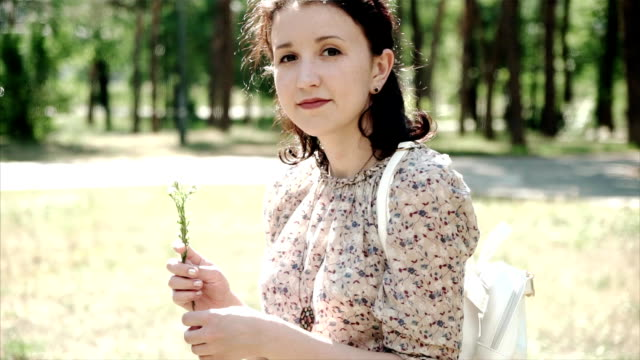 Portrait of young girl sitting on grass holding a flower and looking in camera video
