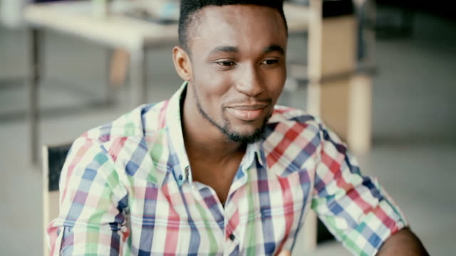 Portrait of young handsome african man. Attractive male actively talks. Guy on an interview for a job video