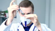 Portrait of young male caucasian doctor pouring a liquid from a syringe to a tube and looking at blue liquid in a test tube video