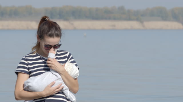 Portrait of young mother walks with her infant on a coast video