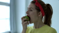 Portrait of young pin up woman eating healthy green apple video