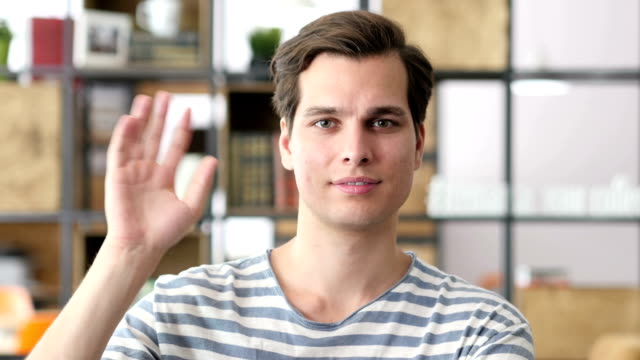 Portrait of young relaxed business man waving hand to camera, designer video