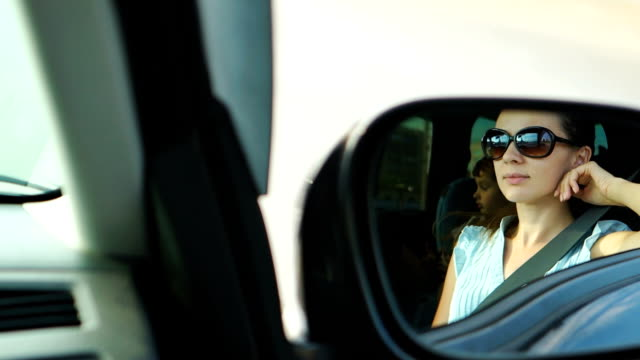 Portrait of young woman in a rearview mirror video