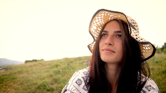 Portrait of young woman on the top of the mountain,close up video