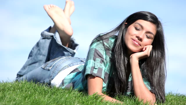 Portrait of young woman relaxing outdoors video