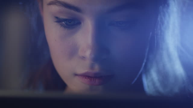 Portrait shot of a beautiful young girl looking a working tablet in the dark. video