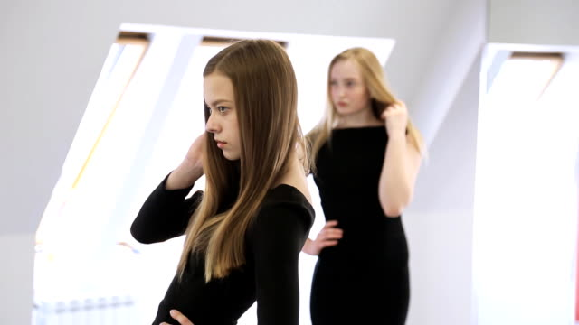 Portrait view of young female posing in model school video