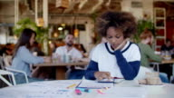 Portret young alone beautiful black woman student overwhelmed by her homework in cafe. Behind him cheerful group of young peoples video