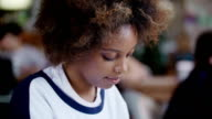 Portret young alone beautiful black woman student overwhelmed by her homework in cafe video
