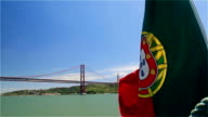 Portuguese flag on a ship on background of 25th April bridge and Jesus statue video