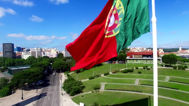 Portuguese Waving Flag in Eduardo VII Park in Lisbon, Portugal aerial view video