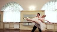 Positive elegant couple practices ballet moves in studio, slowmo video