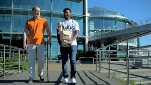 Positive hindu volunteer carring food for a senior man video