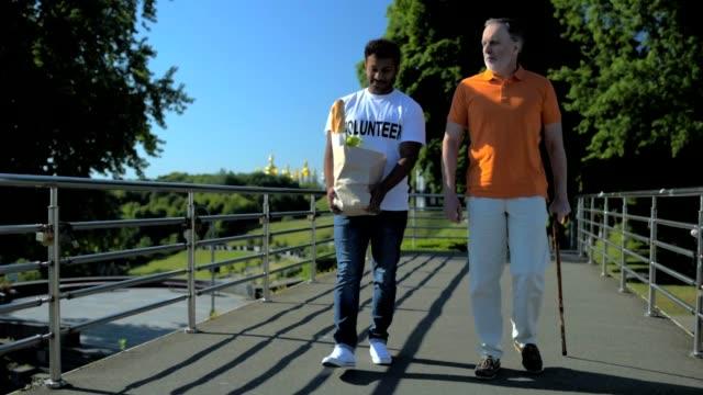 Positive hindu volunteer helping a senior man with a walking stick video