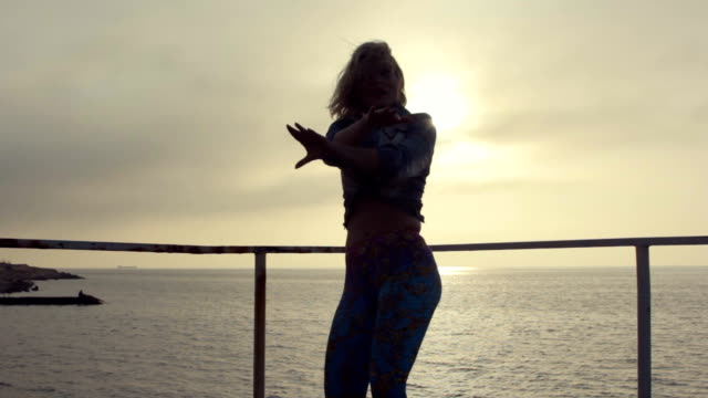 Positive young sexy woman dancing twerk on the pier near the sea at a sunset video