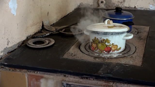pot boil on old rural stove and water flow out burn and hand take lid. video