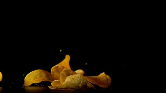SLOW: Potato chips fall on a table. Black background video