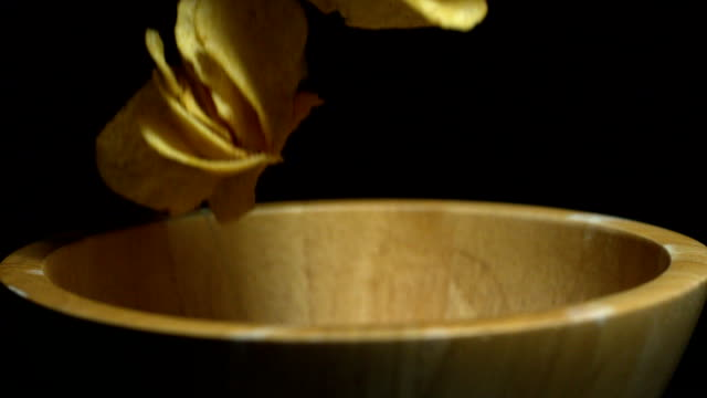 Potato chips falling into wooden bowl video