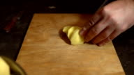 Potato tuber is cut manually with a knife into slices on the Board. video