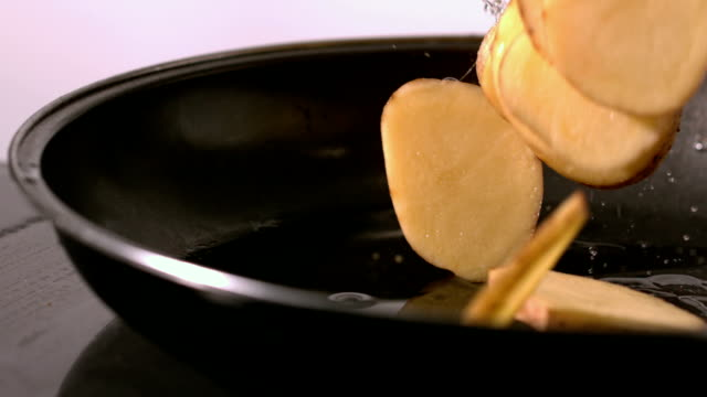 Potato wedges falling in a hot pan video