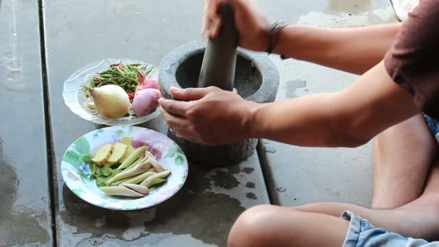 Pounding garlic in mortar for cooking dinner video
