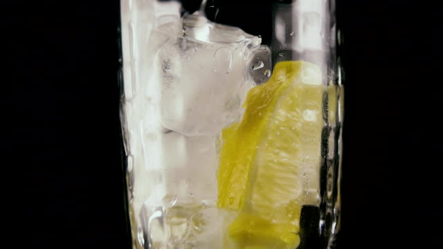 Pour soda into a glass on a black background. Slow motion video
