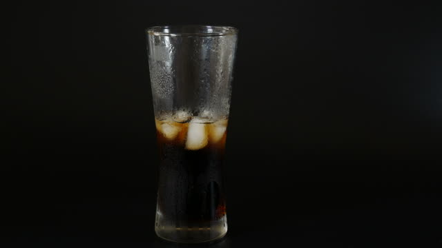 Pour the cola from a plastic bottle into a glass of ice video