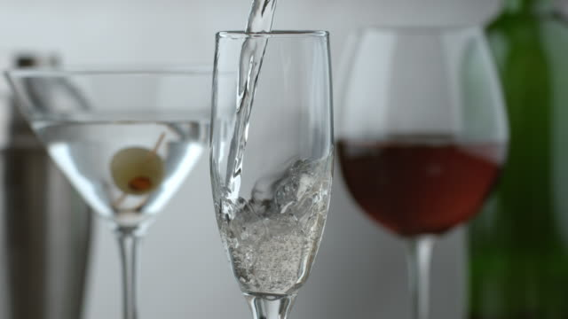 Pouring a glass of champagne with other drinks in background video