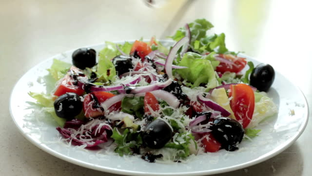 Pouring balsamic sauce onto vegetable salad, close up video