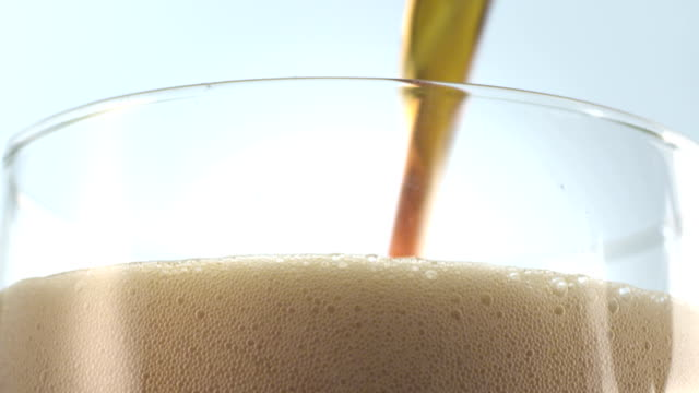 Pouring beer into a glass close-up video