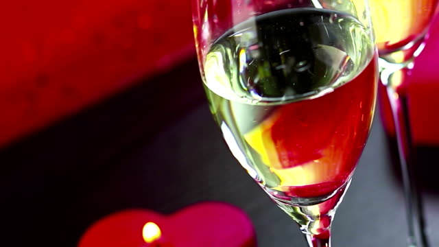 pouring champagne flutes near red candles burning, love and valentine day concept video