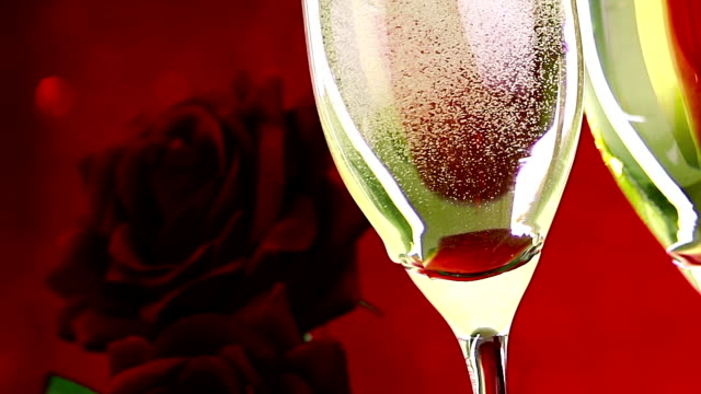 pouring champagne flutes with bubbles near red roses on red bokeh background, love and valentine day concept video