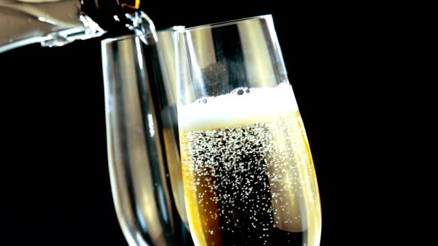 pouring champagne into flutes with fizzy bubbles video