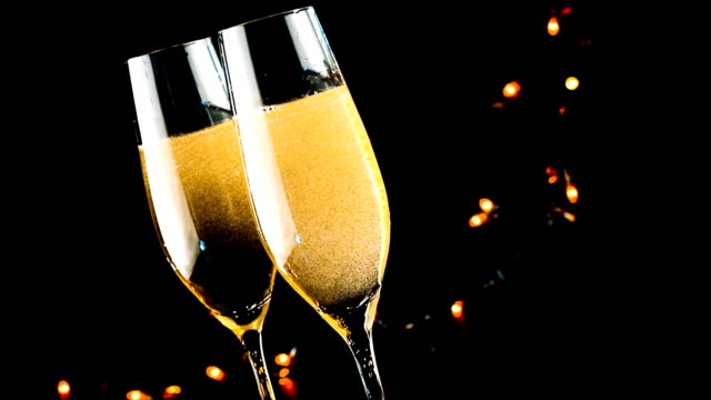 pouring champagne into flutes with golden bubbles on black background, holiday atmosphere video