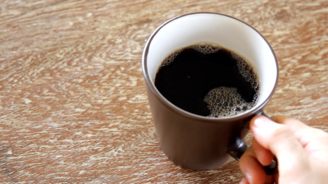 pouring coffee into a cup on wooden table video