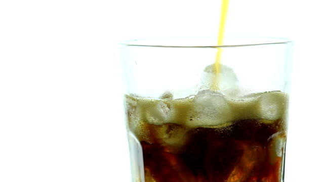 Pouring Cola into rotate glass with ice on white video