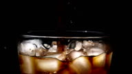 Pouring cola soda into glass of ice with splashes at slow motion on black background video