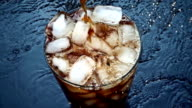 Pouring cola soda into glass of ice with splashes at slow motion video