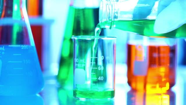 Pouring color liquid into laboratory grassware video