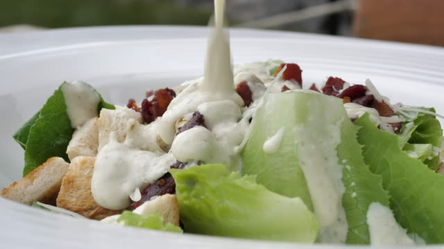 Pouring Cream sauce over salad video