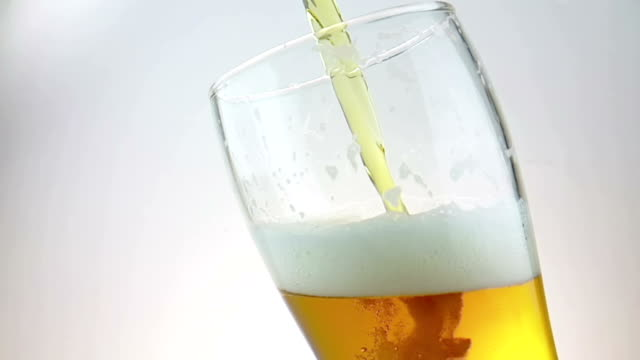 pouring fresh beer with foam into drink pint glass with ice frozen drops, shot slow motion on white background, fun and nutrition food and drink video