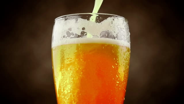 pouring fresh beer with foam into glass on brown background video