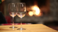 Pouring glasses of wine by fireplace video