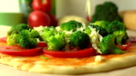 Pouring grated cheese over broccoli. Cooking homemade pizza, part of the set. FullHD close up video video