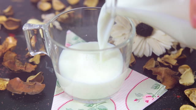 Pouring milk into a cup on vintage table. video