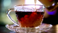Pouring milk into hot black tea, milk spills video