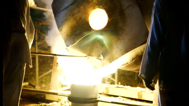SLO MO Pouring of liquid metal in castings while layered white smoke from blast furnaces. Processing steel in iron foundry plant. video