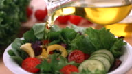 Pouring olive oil onto fresh salad, slow motion video